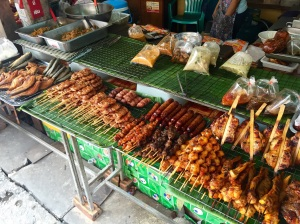 "Many types of foods and meats are available from street vendors in the markets. Meat-on-a-stick is very common; here you can see chicken, sausage, pork, and ground-up fish rolled into balls (on a stick). Freshly grilled, this is Asia's form of ""fast food."" (Also in the photo are bags of soups, noodles, and curries to-go.)"
