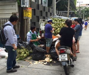 Coconuts are often picked right off the tree and sold from a street vendor or out of the back of a truck, like here, with people lining up to get them fresh.