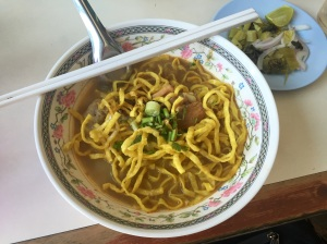 Khao Soi Gai is a popular coconut curry soup with fried/crispy noodles eaten in northern Thailand. Onion, chives, and lime can all be added for flavoring or as a garnish.