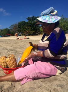 Balinese woman peeling a large mango on the beach in Bali.